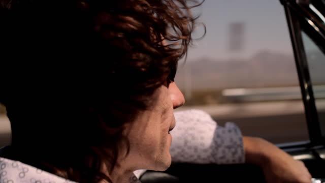 A man's brunette hair blows in the wind as he drives a convertible along a desert highway.