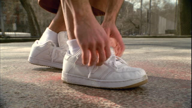 CU Man's feet on basketball court as he ties the laces on his white sneaker/  Harlem, New York