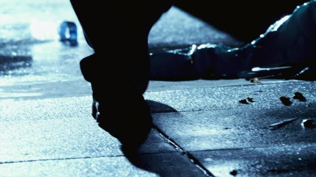 CU Man's feet walk down dark, wet alleyway