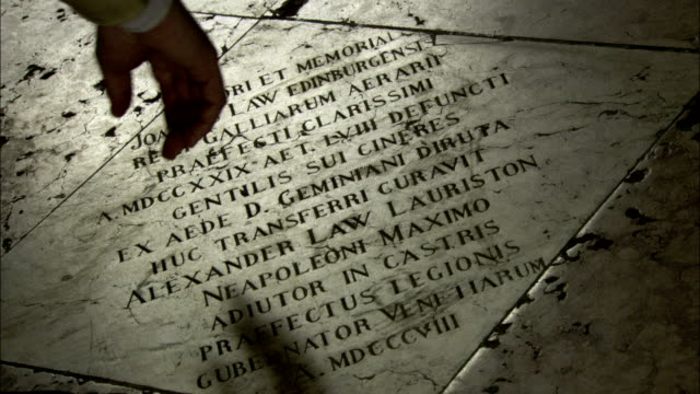A man's finger traces words carved into a marble funeral plaque in Venice. Available in HD.