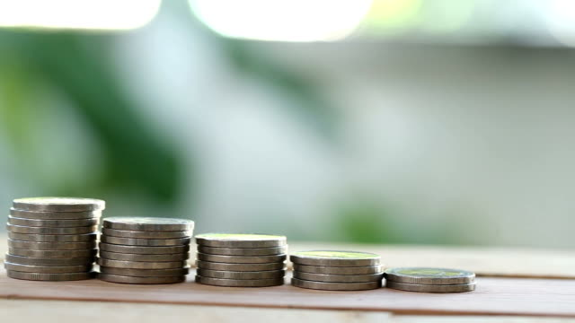 Man's hand caught out a coin on a pile coin for reducing the number concept of business growth.