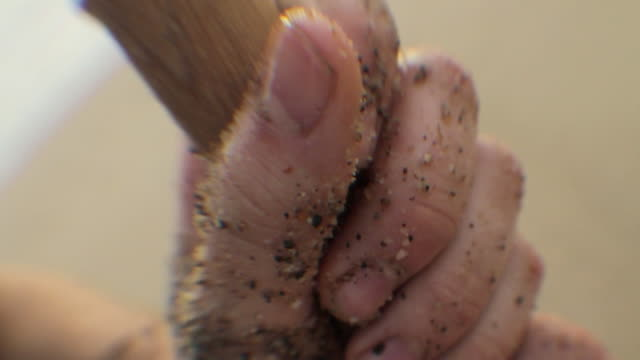 CU SELECTIVE FOCUS Man's hand covered with sand gripping shovel handle / Los Angeles, California, USA