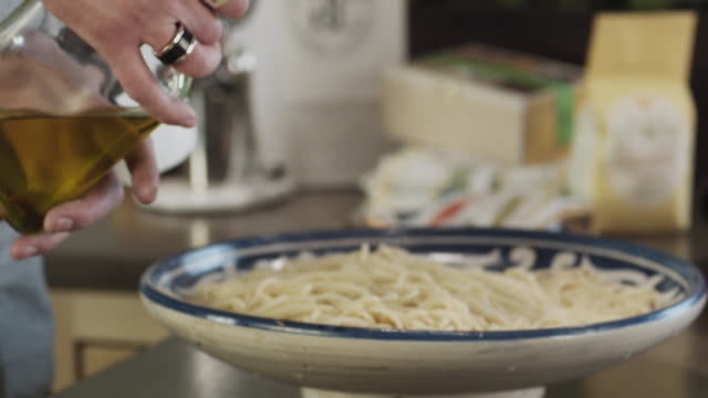 CU SLO MO Man's hand dressing pasta with olive oil / New York City, New York, USA
