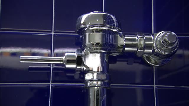 A man's hand flushes a public toilet.
