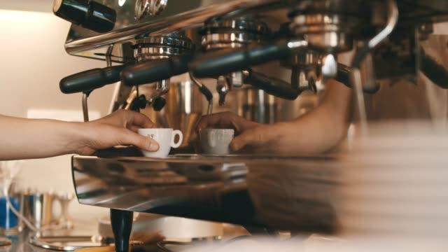 Iemands hand hebt koffiekopje op koffiemachine