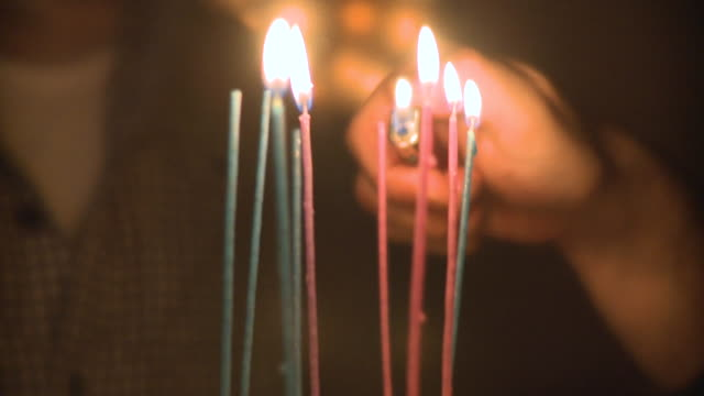 CU SELECTIVE FOCUS Man's hand lighting candles on coconut birthday cake, New York City, New York, USA
