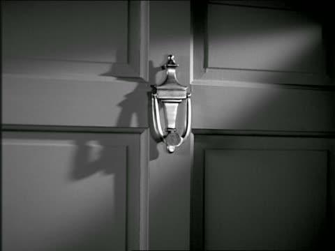 B/W 1937 man's hand rapping door knocker three times