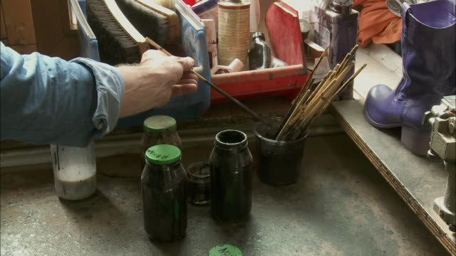 CU Man's hand taking paintbrushes from jar / Brussels, Belgium