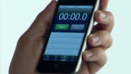 ECU man's hand using stopwatch application on mobile phone / starts and stops timer / London
