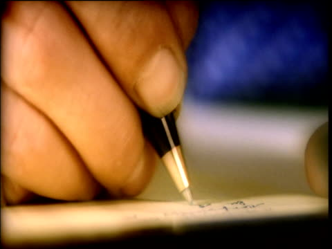 Man's hand writing letter on note pad
