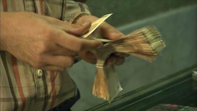 CU Man's hands counting money in currency exchange, Grand Bazaar, Isfahan, Iran