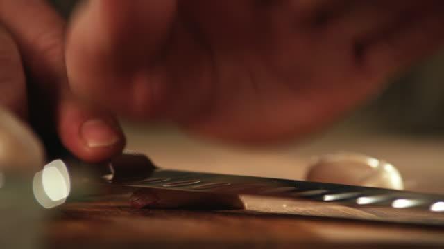 ECU, Man's hands crushing garlic with kitchen knife
