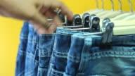 Mann-Hand, die mit jeans rack