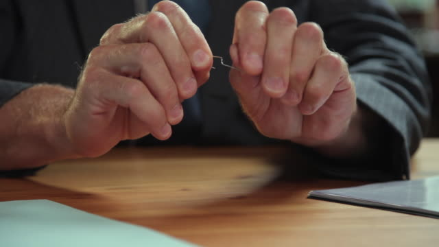 CU Man's hands unfolding paper clip at desk / Portland, Oregon, USA