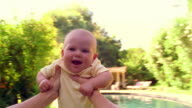MS man's point of view arms holding smiling baby spinning around outdoors