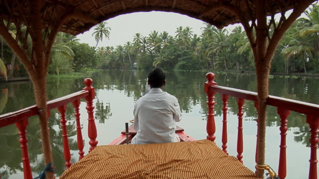 MS, Mans steering boat on Backwaters of Kerala, rear view, India