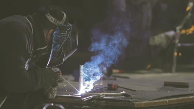 Arbeider met beschermend masker lassen van metaal in een fabriek.