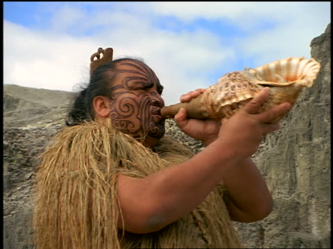 Maori Haka performer blowing through conch shell + turning / Rotorua / N. Island / New Zealand