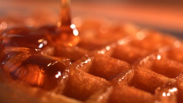 CU SLO MO Maple syrup being poured on waffle top from above / Manchester, United Kingdom