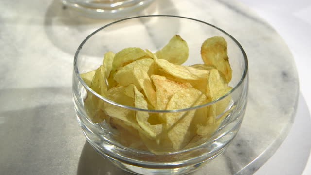 A marble Lazy Susan turns to reveal a larger glass bowl of crisps.