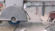 MS PAN marble shop workman with handheld control box checking automated miter saw cutting through marble slab with water injection  / Thousand Palms, California, USA