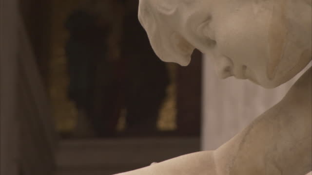 A marble statue in the Athena Fountain depicts a woman extending her right hand..