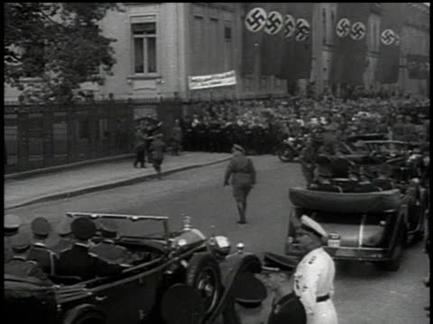 March 13 1938 BW parade of open staff cars carrying Wehrmacht officers past swastika flags and pedestrians / Vienna Austria