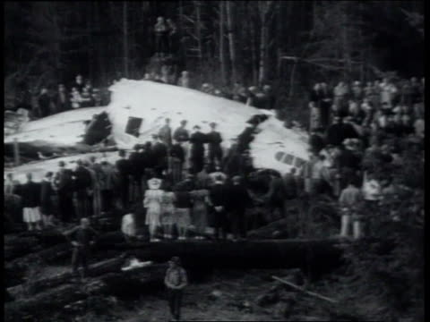 March 20 1939 MONTAGE Emergency personnel examining aircraft wreckage / Alder Washington United States