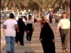 March 31 1999 WS Pedestrians walking and jogging along a wide sidewalk with vehicle traffic and palm trees in the background / Doha Qatar