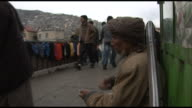 March 4 2005 MS Beggar on the side of the road with many people walking by / Kabul Afghanistan