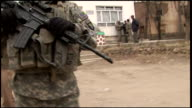 March 6 2009 CU US Army soldier standing guard with machine gun while civilians and soldiers are talking in the background / Afghanistan