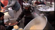 March 9 2009 HA Cooks scooping and preparing rice outdoors / Kandahar Afghanistan