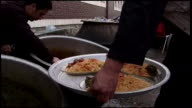 March 9 2009 TS Cooks spooning food onto metal trays and passing them on to be served / Kandahar Afghanistan