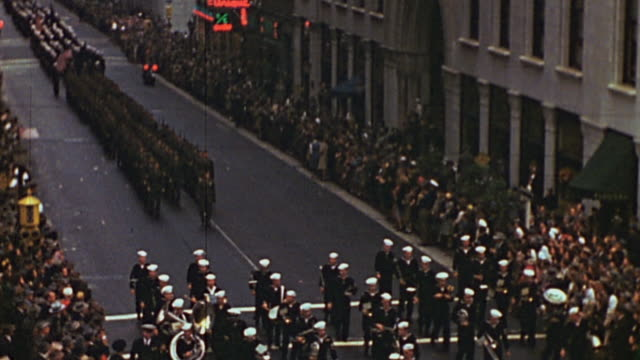 TU Marching band leading parade of soldiers in formation down city street thronged with spectators / New York City New York United States