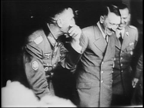 Marching German Army fills frame / Adolf Hitler and German leaders look at map and smile / Benito Mussolini exits plane and is greeted by Hitler /...