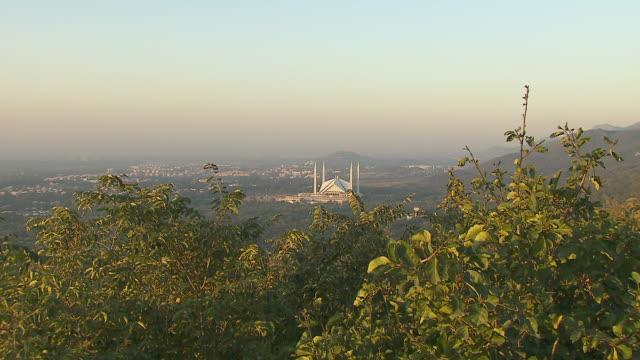 HA XWS Shah Faisal Masjid w/ four minarets in distance vegetation branches FG ZI Partial Masjid South Asia capital city of Islam contemporary Islamic...