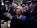Margaret Thatcher MP arrives to take office car driving down Downing Street large cheers and some boos heard / Thatcher out of car wearing blue suit...