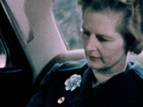 Margaret Thatcher works on paperwork while being driven in her official car 1970's