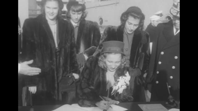 Margaret Truman in fur coat and large corsage signs guest book followed by Alice Roosevelt Longworth as the two arrive on the USS Missouri for Navy...