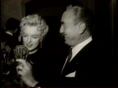 Marilyn Monroe is greeted by cheering people / She receives a Warner Bros key and a large bouquet of flowers from Jack Warner / Marilyn Monroe speaks...