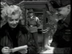 Marilyn Monroe walking with troops / officer giving Marilyn some mail / soldiers lining up to meet Marilyn / sign saying 'Welcome Marilyn Monroe'...