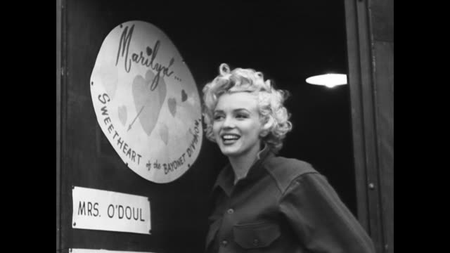 Marilyn standing at stage entrance waving / GI adjusts the lights on the stage