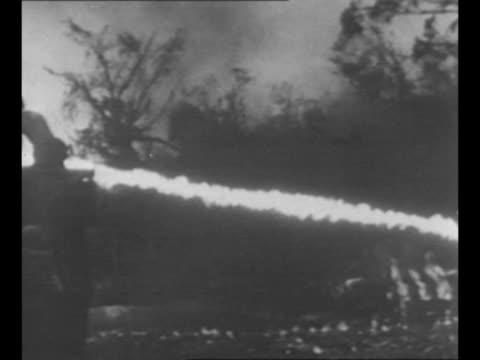 US Marine aims flamethrower into an underground pillbox during World War II battle for Peleliu Island / Marines fire long stream of flame pan...