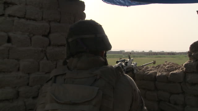 A U.S. Marine aims his M240B machine gun toward stone buildings in an Afghan village.