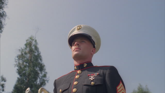 A Marine bugler plays taps at a funeral.