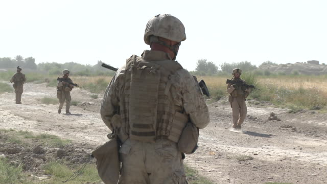 A U.S. Marine fire team patrols on a dusty country road.