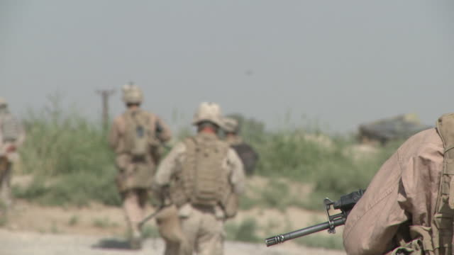 A U.S. Marine Humvee passes a squad of Marines on patrol.