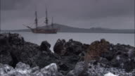 Marine iguana bobs head on rock, replica of HMS Endeavour rests at anchor.