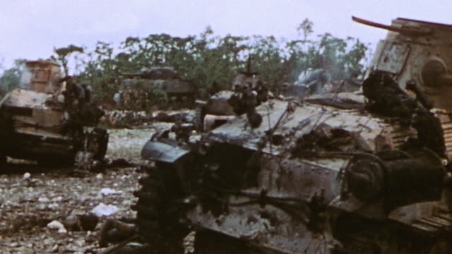 Marines examining debris and wreckage of Japanese tanks