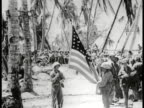 Marines gathered on beach raising American flag on rope tied to coconut tree VS Marines saluting WWII World War II